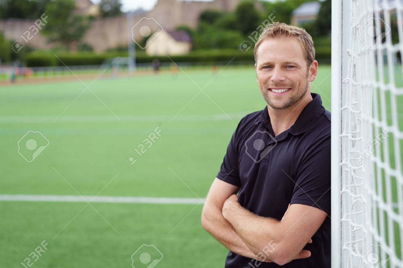 Relaxed happy football coach leaning on the goal posts with folded arms grinning at the camera, close up with copy space Stock Photo - 63969698