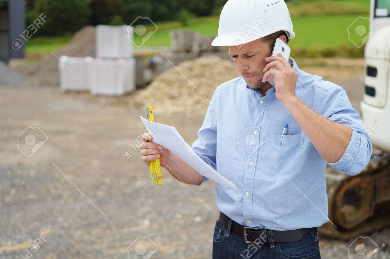 Architect or builder standing at a building site in his hardhat talking on a mobile phone as he reads a document in his hand - 65436650