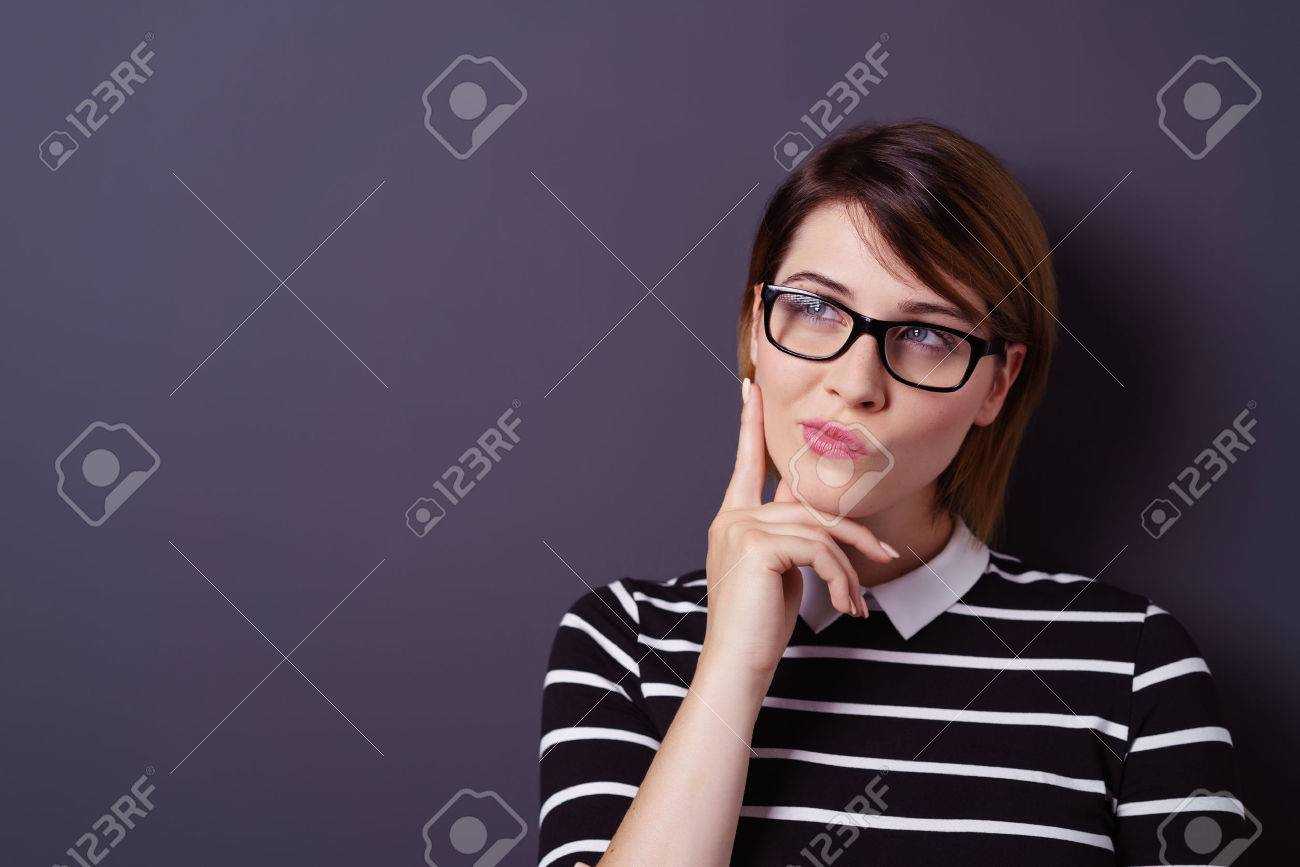 Single young attractive thinking woman with fingers on chin and short hair over dark background Stock Photo - 63969781