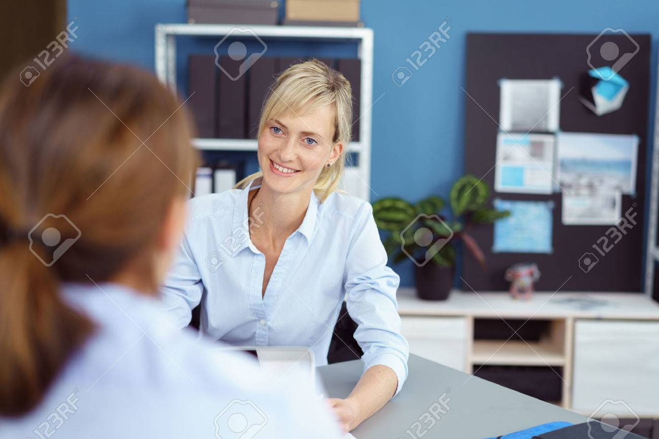 Attractive young woman in a business interview for a job vacancy listening attentively to the female interviewer with a smile, over the shoulder view - 63969825