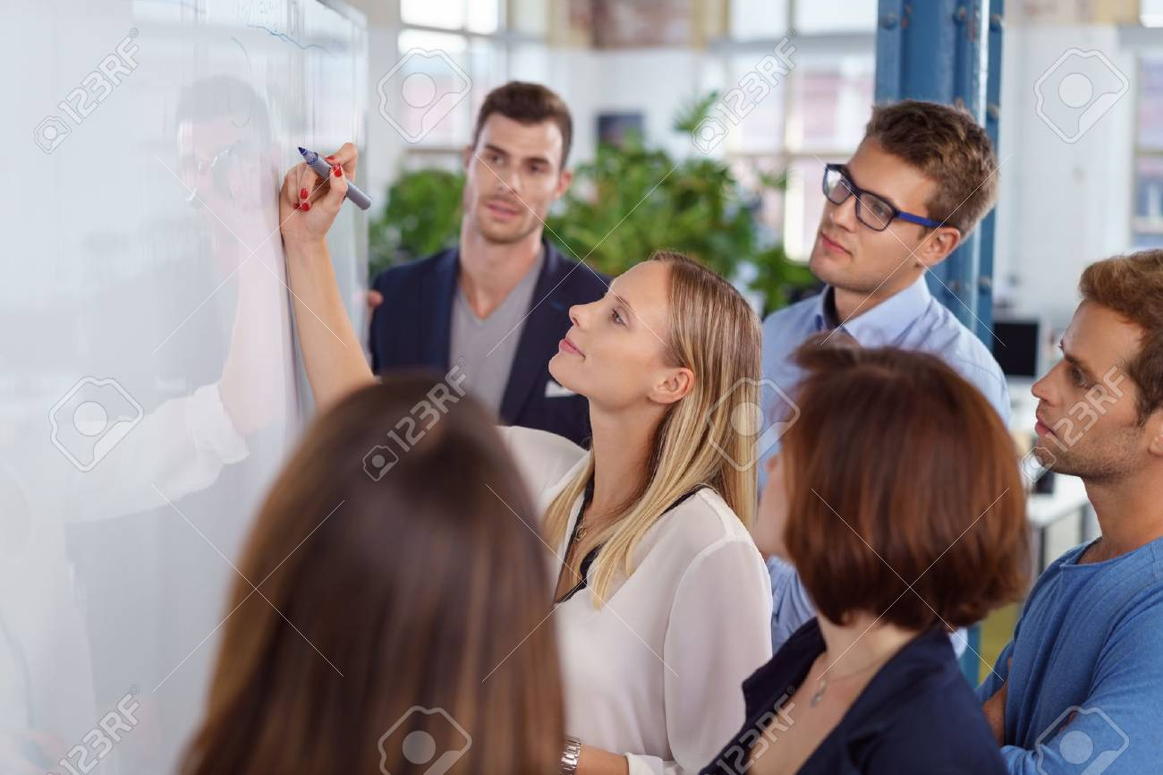 Confident blond woman writing on blank white board with fellow young adult workers standing around smiling - 65443182