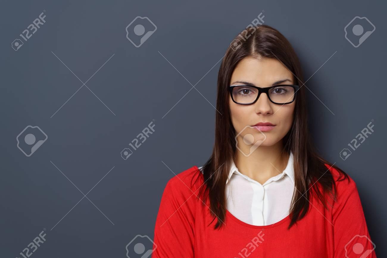 c18e967d8ea347 Ernstige intense jonge vrouw draagt   een bril staren naar de camera met  een ondoorgrondelijke