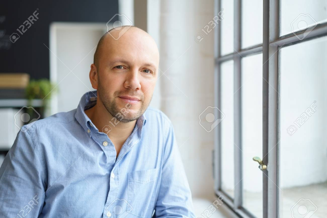 businessman standing close to a window with a smile - 68431248