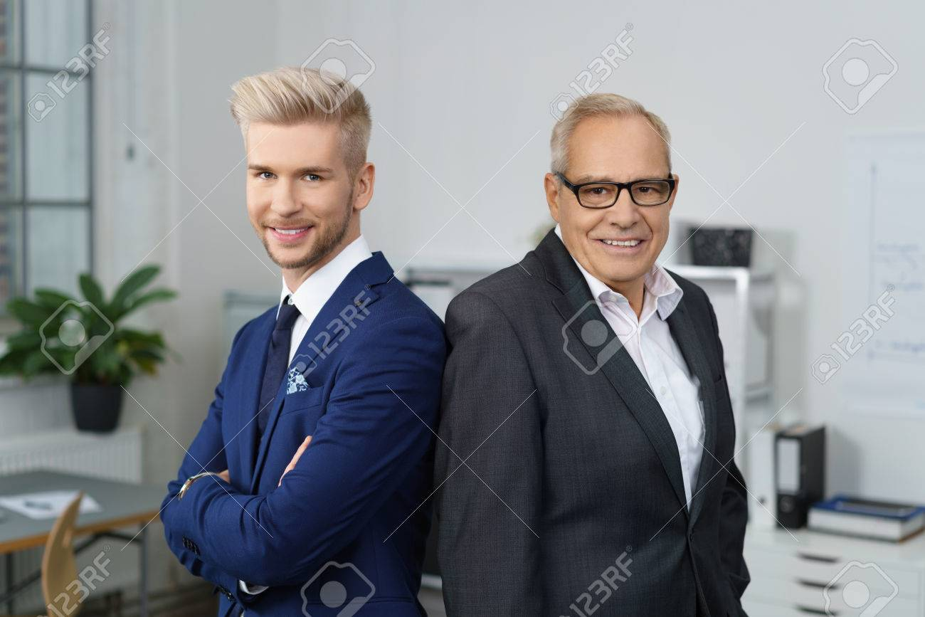 Confident successful business partners posing together with a stylish young man and his older mentor standing back to back smiling at the camera - 68433247