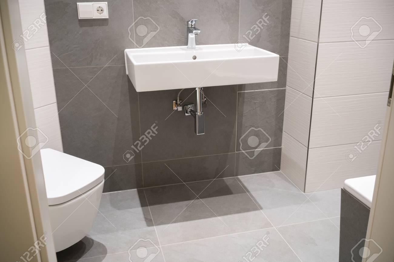 Salle de bain moderne et élégante avec un décor neutre dans les tons de  gris et beige avec un grand lavabo rectangulaire monté au mur et des  toilettes