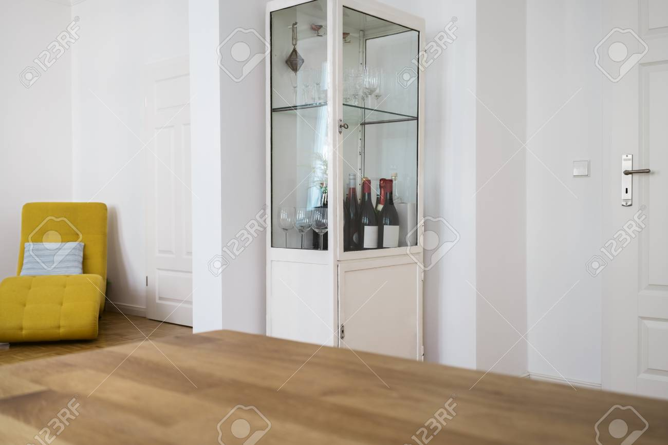 Glass fronted wine cabinet in the corner of a living room interior..