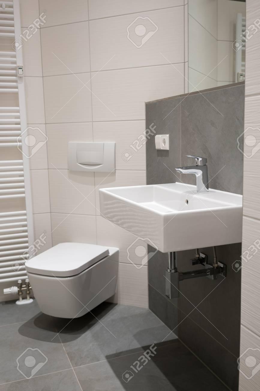 Accesorios de plomería modernas en un pequeño cuarto de baño con un lavabo  rectangular y aseo en una pared de azulejos y el suelo en tonos neutros