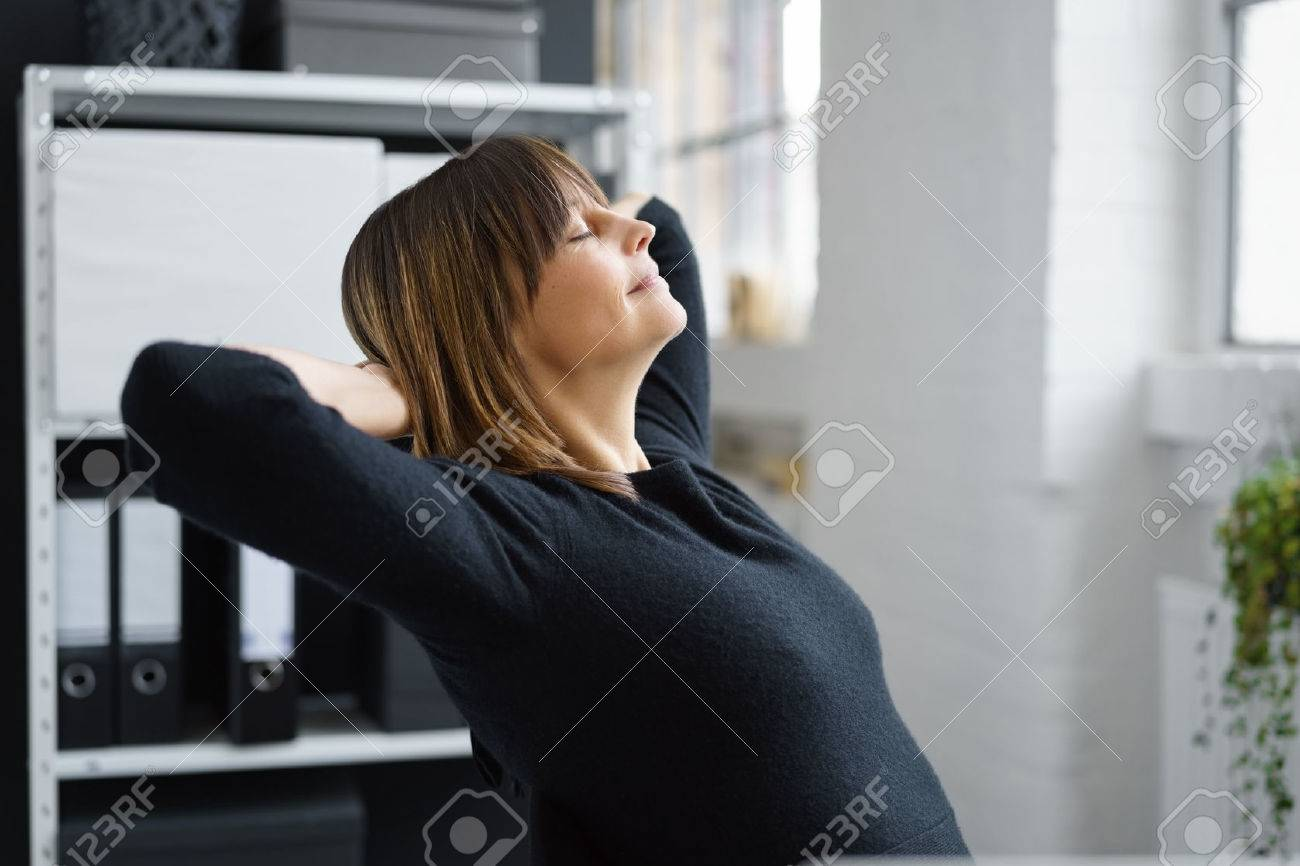 Attractive businesswoman taking a break to relax and de-stress leaning back in her chair with her eyes closed, profile view - 69584154