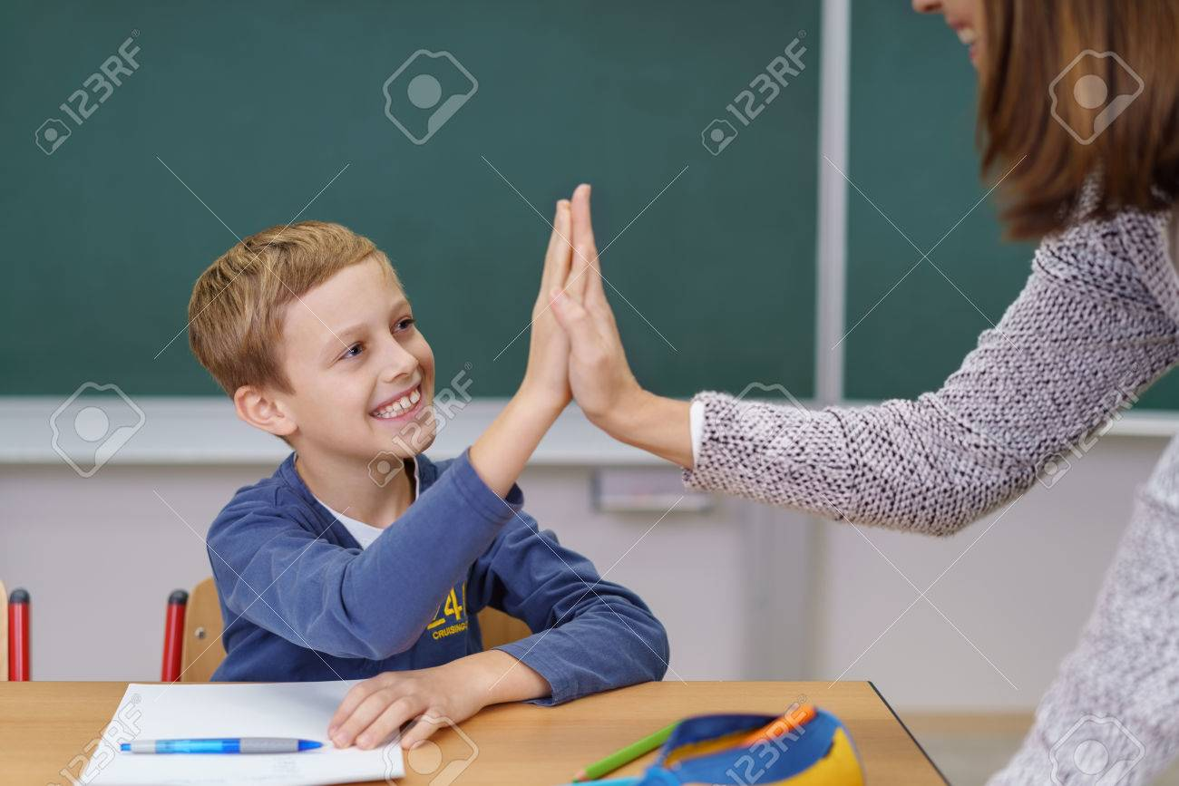 Teacher and happy grinning young student doing a high fives as the schoolboy finally succeeds in understanding something Banque d'images - 70439909