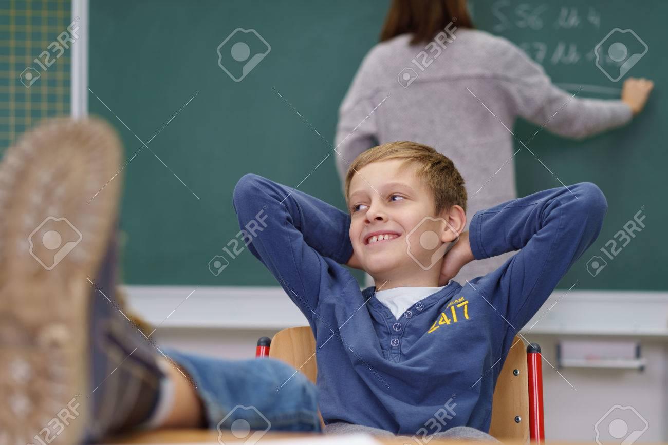 Jeune garçon avec ses pieds sur le bureau et un sourire espiègle