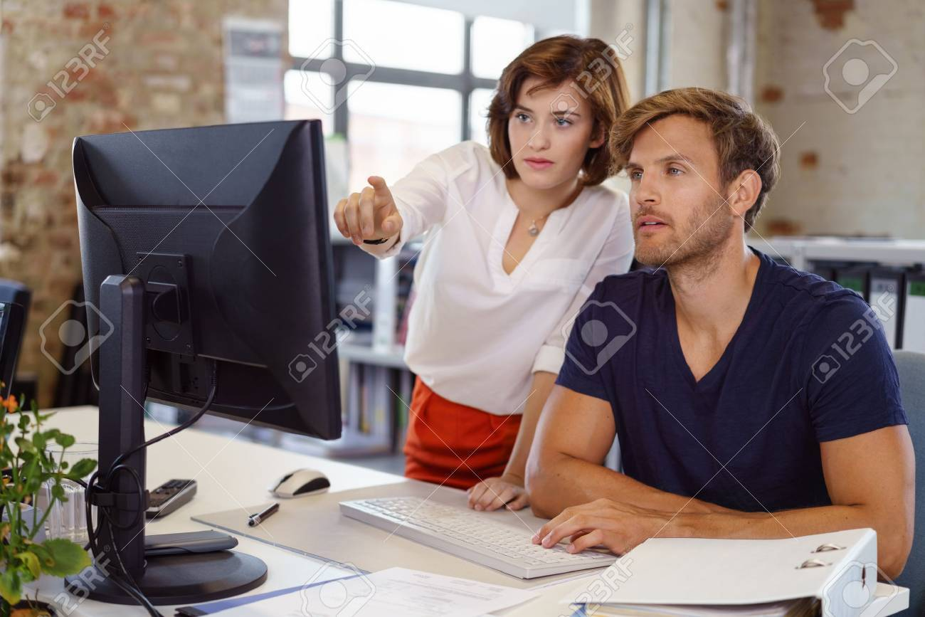 Woman showing something to young man colleague pointing her finger to computer screen, both looking at monitor - 70547138