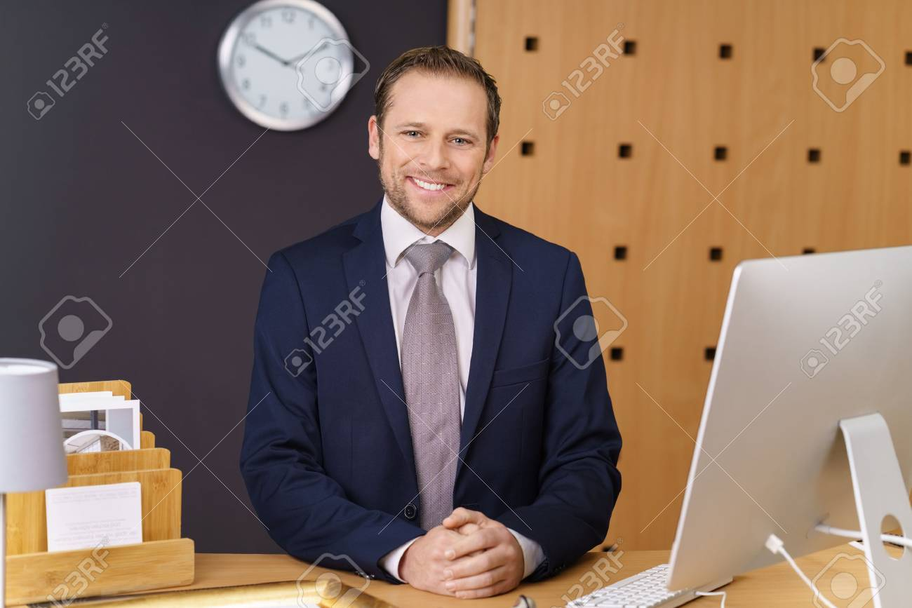 Confident young hotel manager with a welcoming smile standing waiting to greet visitors at the front desk of a luxury hotel - 72188366