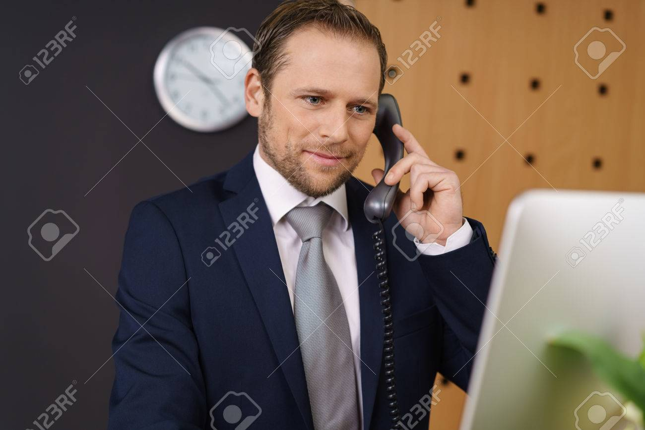 Handsome young hotel manager checking information on his desktop computer at the front reception desk as he listens to a call from a customer Standard-Bild - 72188382