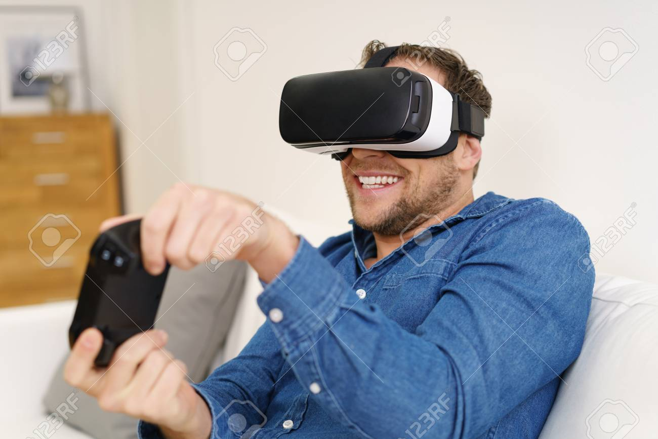 ac8af867fee1 Stock Photo - Young man playing in virtual reality video games with  joystick sitting on couch at home in VR headset