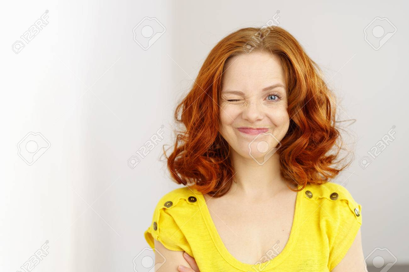 Cheeky Playful Woman With Shoulder Length Red Hair Standing Winking