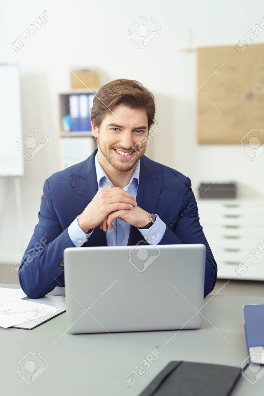 Friendly Young Businessman With A Happy Smile Sitting At His
