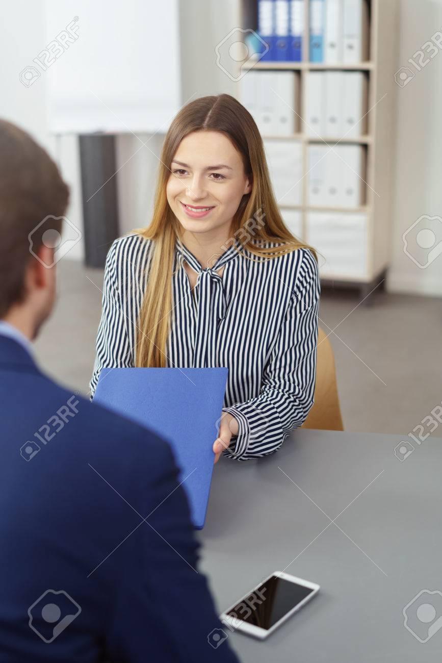 Junge Frau, die ihrem Manager oder Rekrutierungsoffizier ihren Lebenslauf  mit einem Lächeln präsentiert, während
