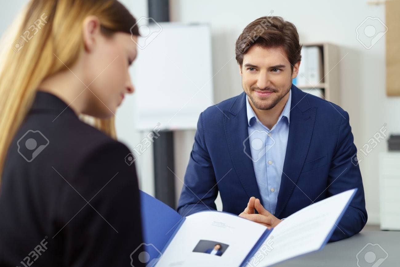 Handsome young businessman in a job interview smiling as he watches a female business executive reading his CV in a file - 76674016