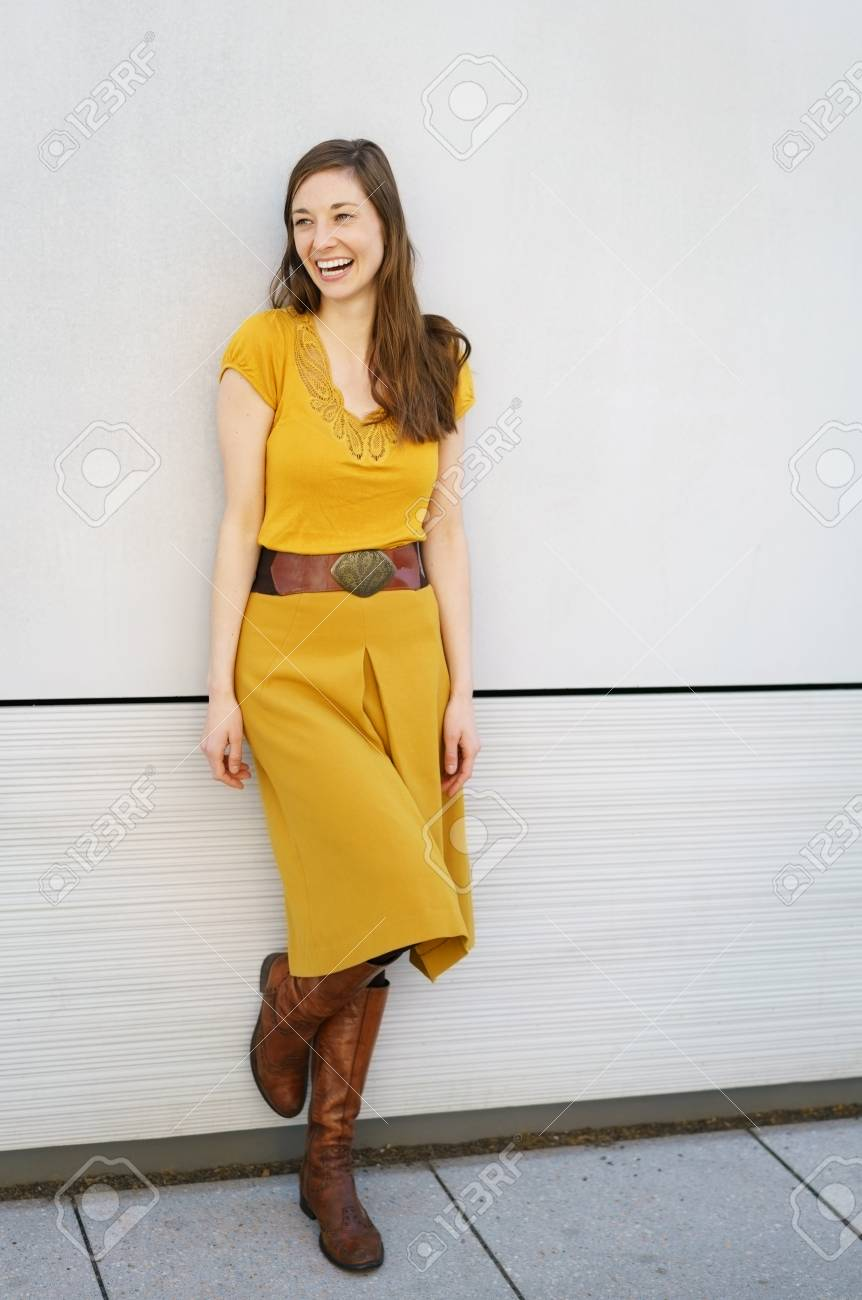 Laughing Sexy Young Woman Posing On A One Foot As She Leans Against