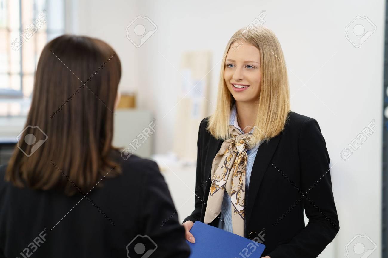 Hoffnungsvolle junge Frau in einem Vorstellungsgespräch, das dem weiblichen  Interviewer mit einem nachdenklichen Lächeln zuhört