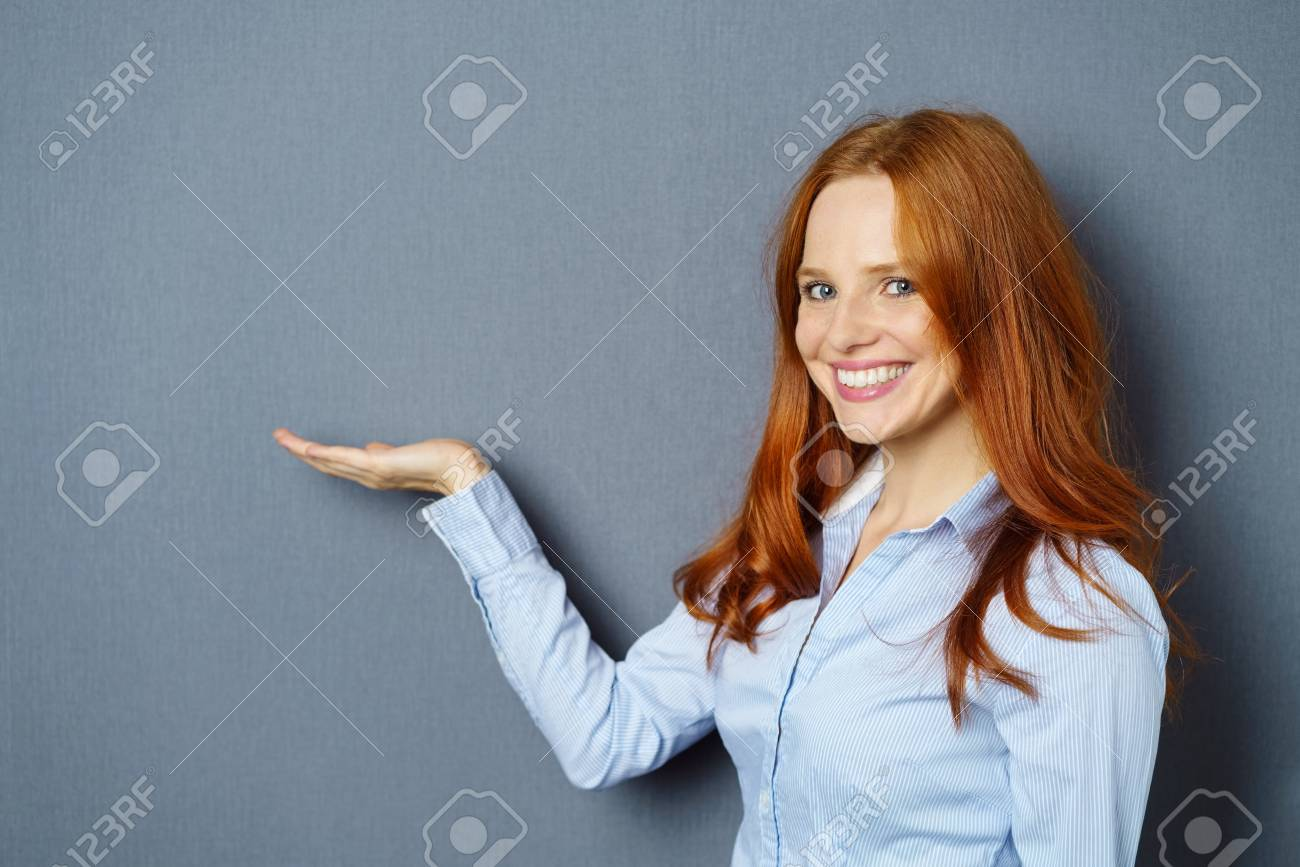 Smiling young woman holding out her hand with the empty palm up over blank copy space for your product placement - 85136283