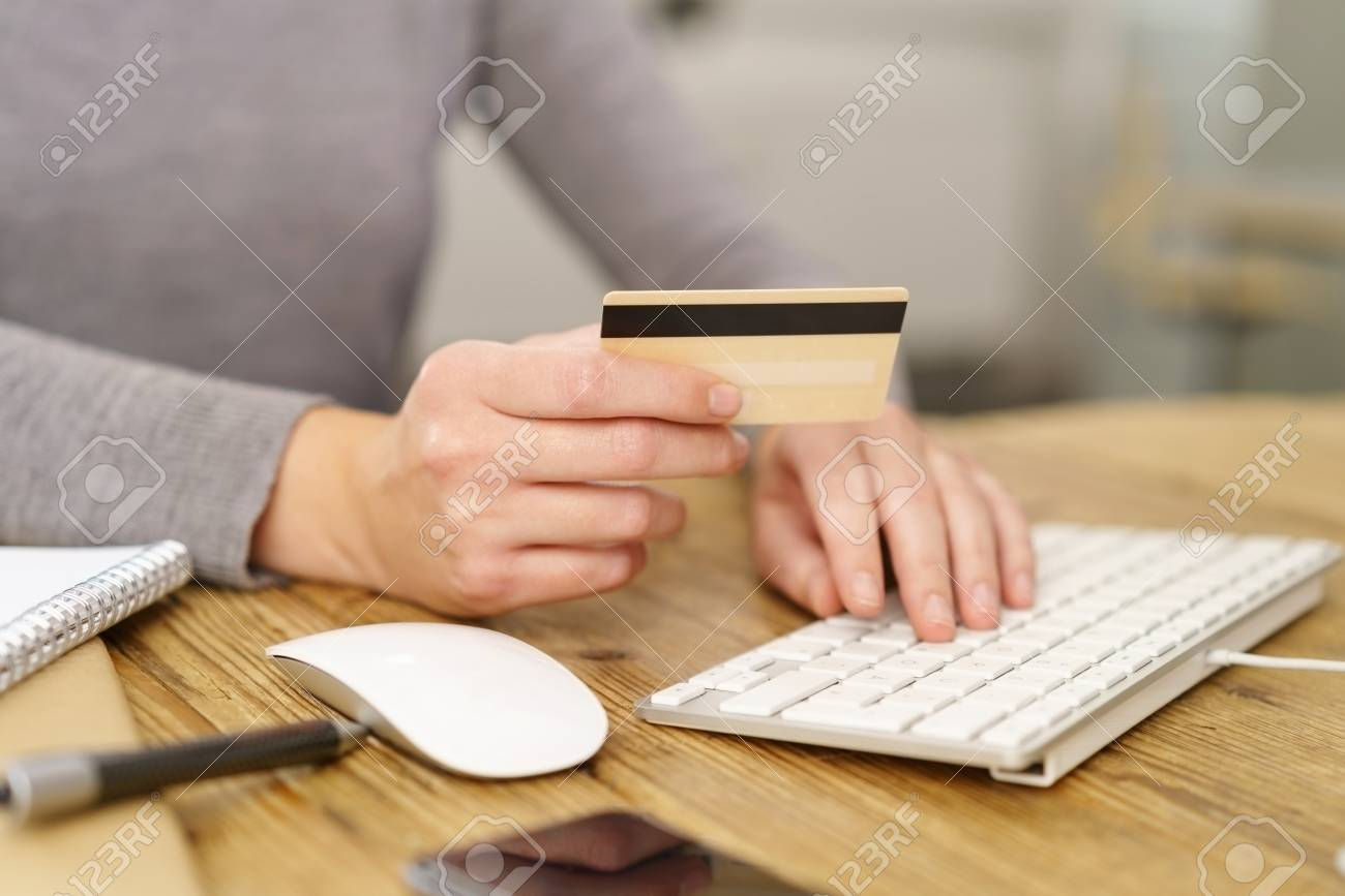 Woman making online purchases entering her bank card details as she completes her shopping - 89273563