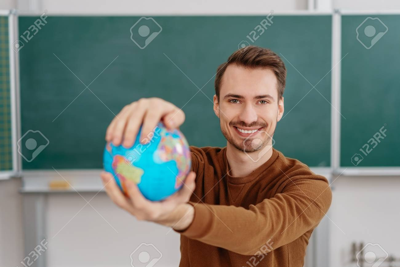 Portrait of young smiling man holding globe against blackboard in classroom - 91861057