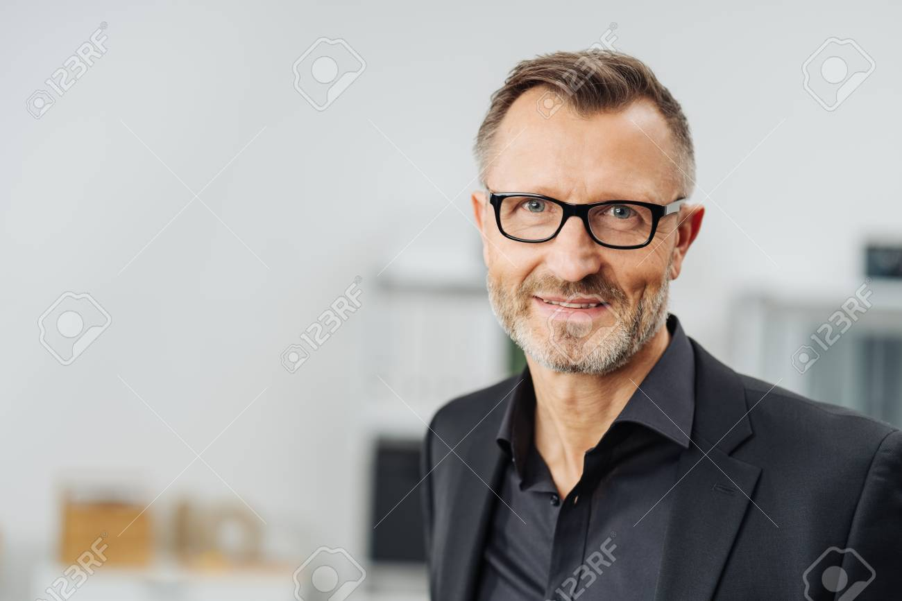 Middle-aged businessman wearing glasses smiling at the camera in a head and shoulders portrait with copy space - 94754373