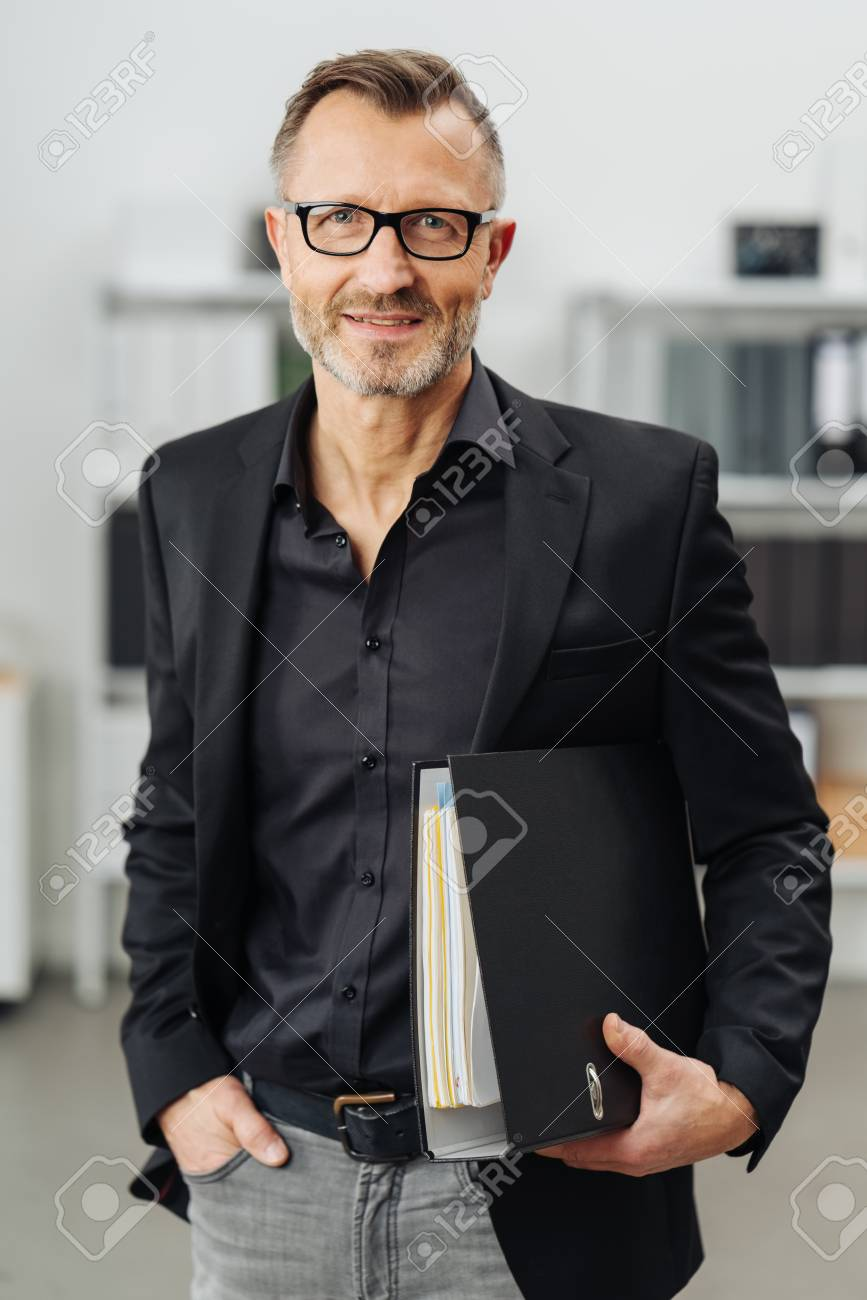 Successful businessman carrying an office binder under his arm as he stands smiling at the camera with a thoughtful expression - 94779348