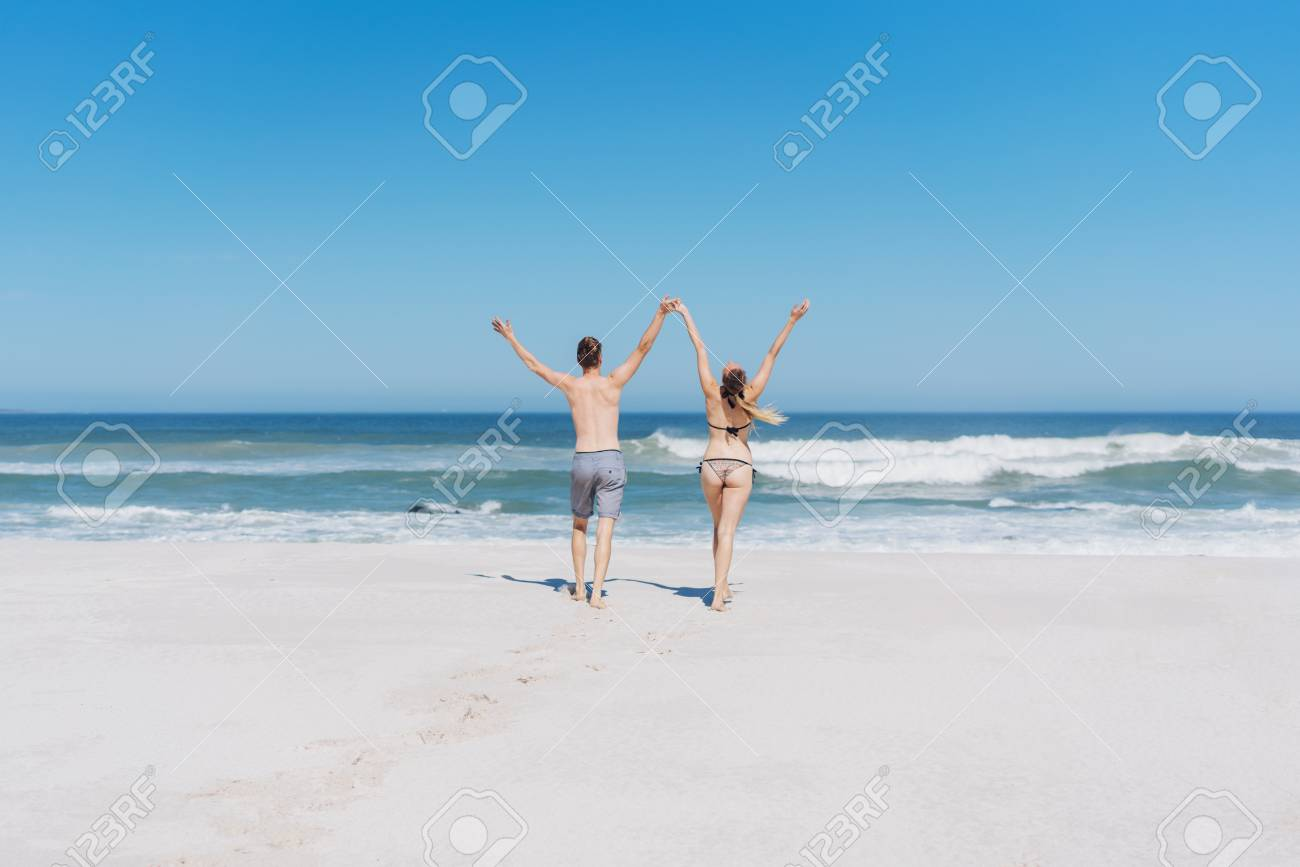 616a3523c2 Joyful young couple running towards the ocean in their bathing costumes  over a sandy tropical beach