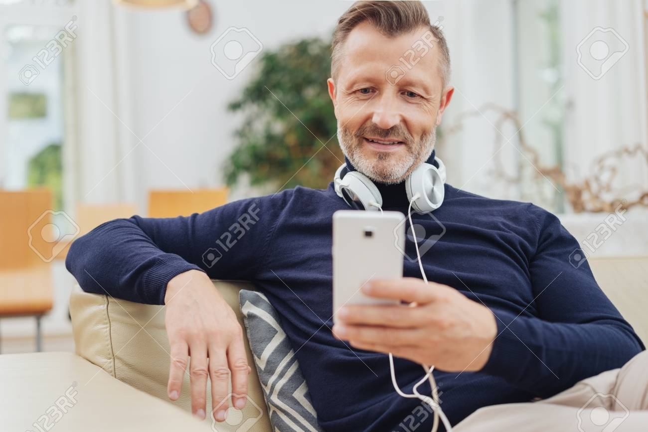 Middle-aged man relaxing listening to music on his mobile phone with stereo headphones around his neck - 115108928