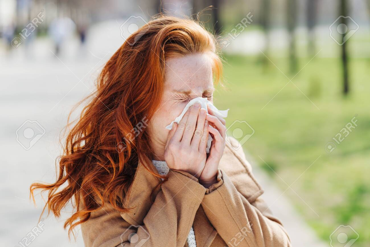 Young woman suffering from hay fever or pollen allergy in early spring blowing her nose on a tissue outdoors in a park - 122224636