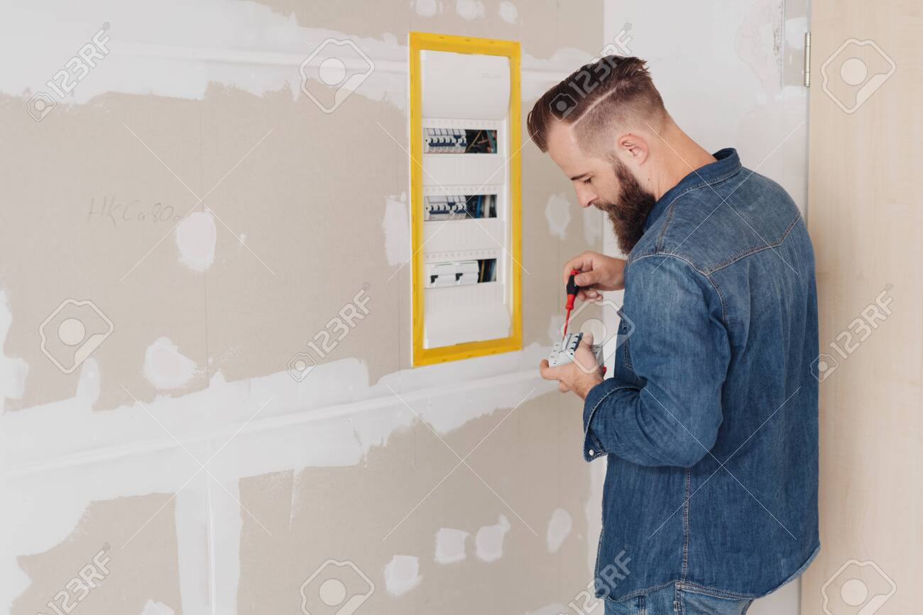 young electrician installing a fuse box or panel in a newly clad.. stock  photo, picture and royalty free image. image 126305359.  123rf