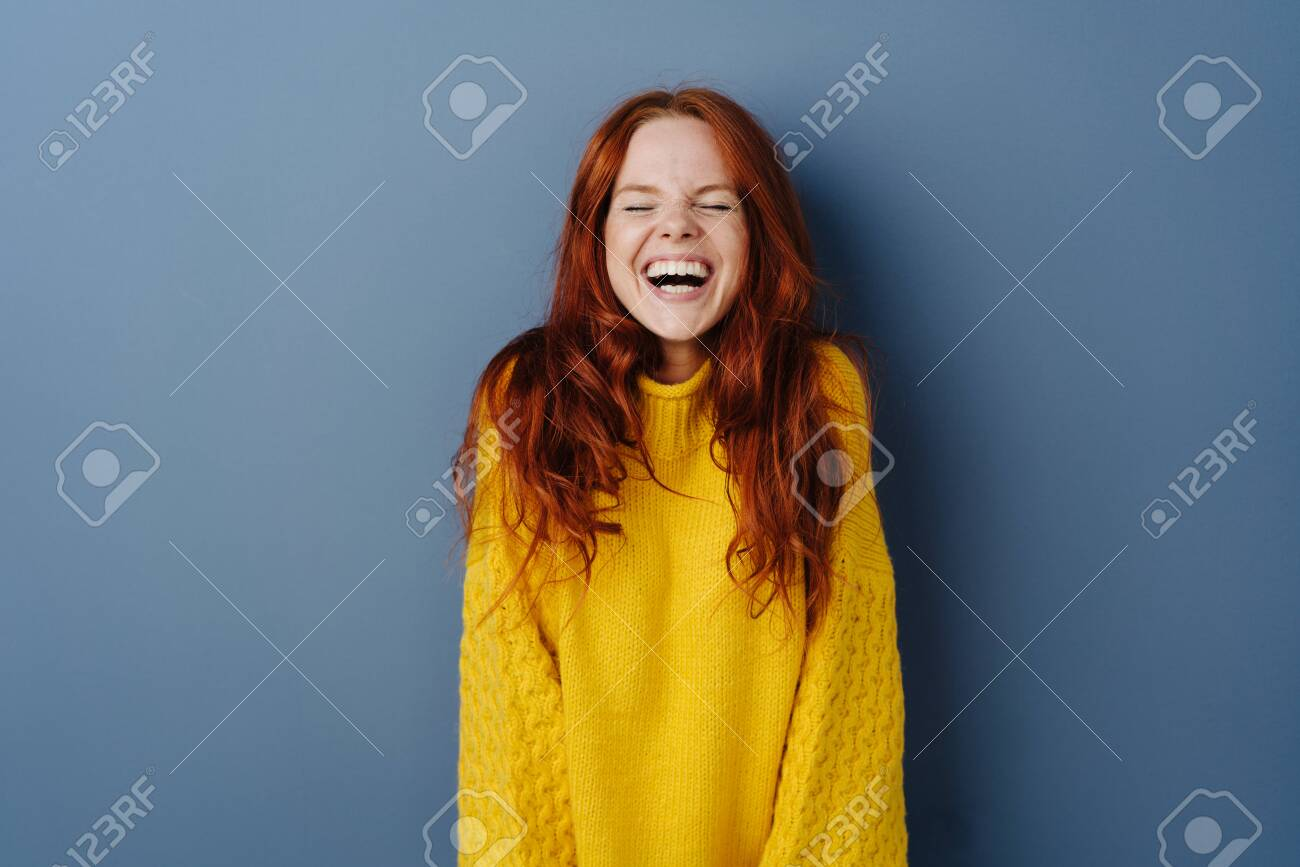 Quirky young woman screwing up her eyes as she enjoys a hearty laugh at a joke over a blue studio background with copy space - 132112334
