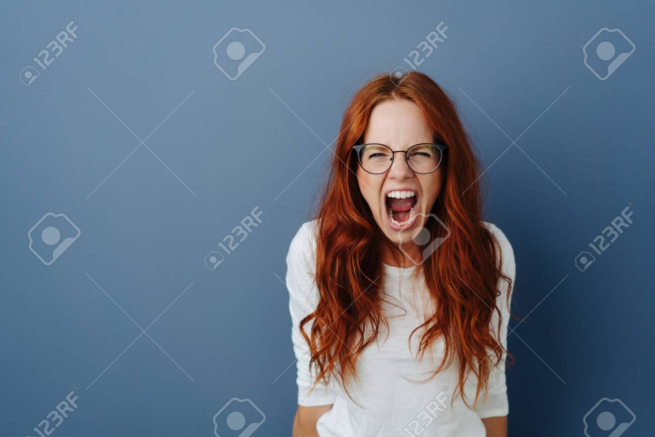 Angry young woman throwing a temper tantrum yelling at the camera with a furious expression over a blue studio background with copy space - 133794608