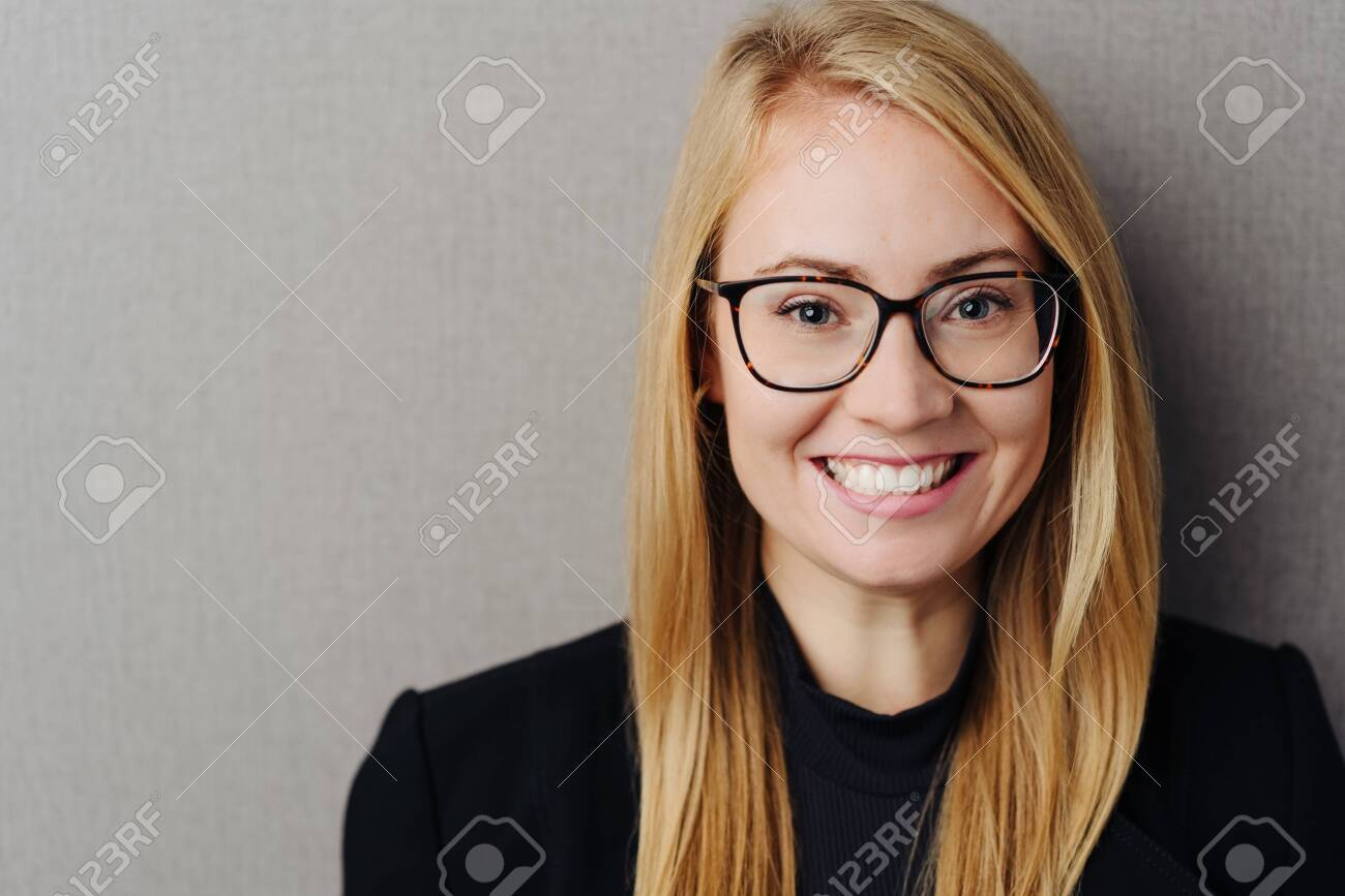 Happy young blond woman wearing glasses looking at the camera with a toothy grin over a grey studio background with copy space - 137632702