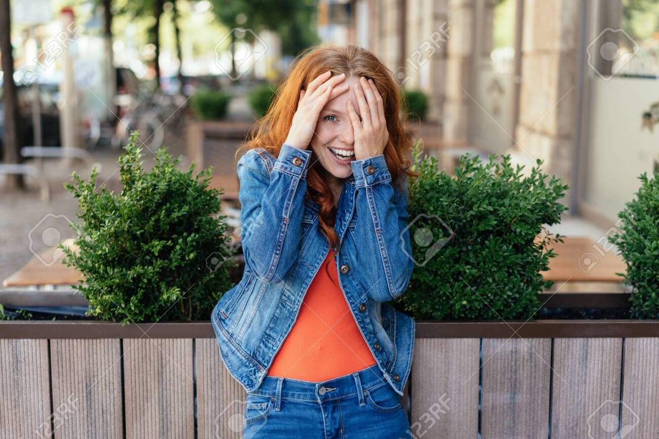 Cute embarrassed young woman covering her face as she laughs at the camera on a quiet urban street - 154410519