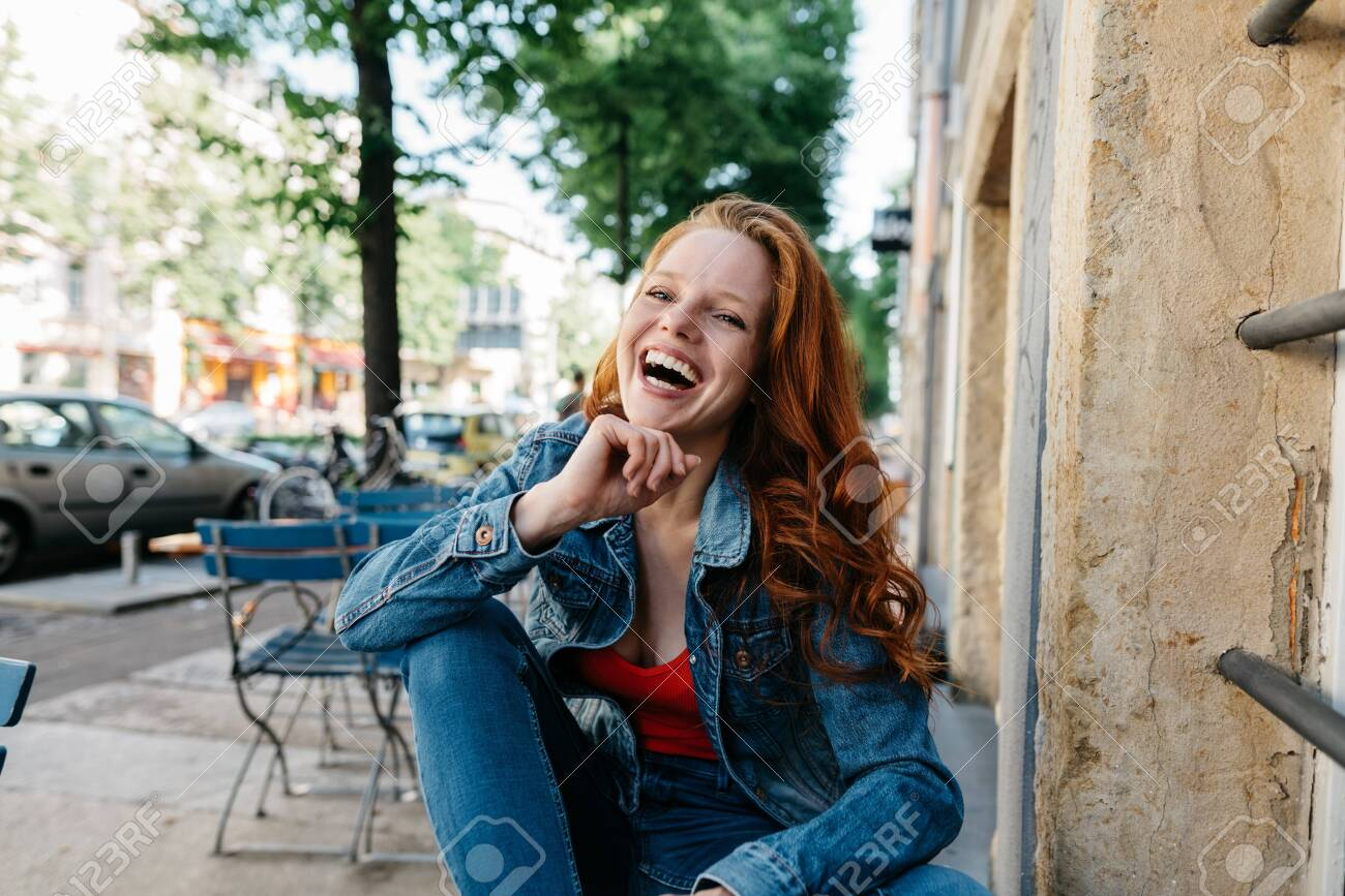 Vivacious young woman laughing uproariously at the camera as she enjoys a good joke while seated on top of a table at an empty outdoor restaurant in town - 154410520