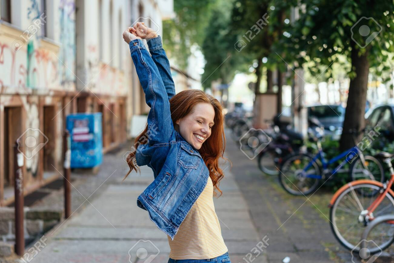 Young woman celebrating with raised arms and a happy smile on an urban street as she turns back towards the camera - 154410521