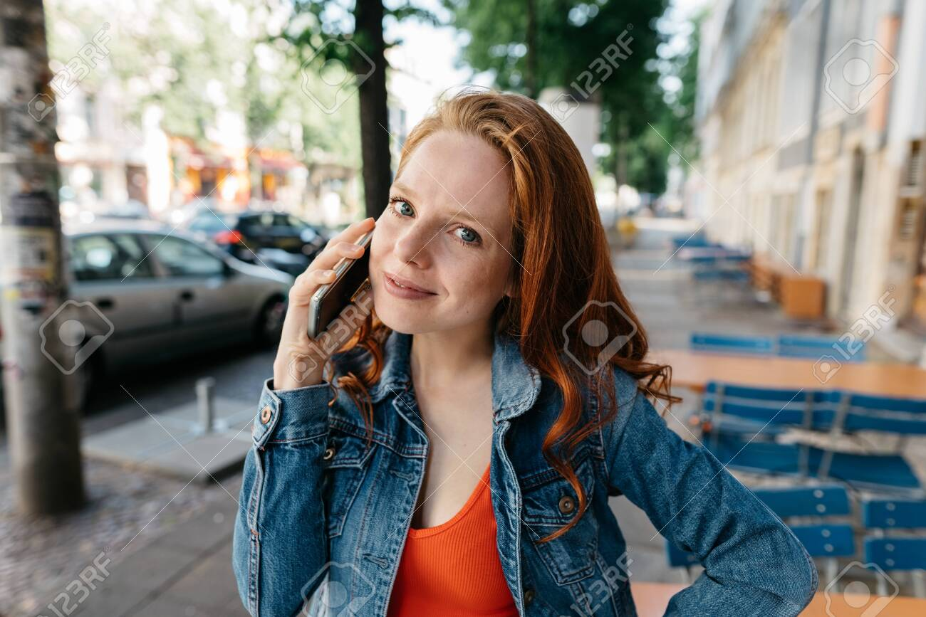 Thoughtful young woman listening to a call on her mobile phone in a quiet street in town in close up smiling quietly at the camera - 154410525