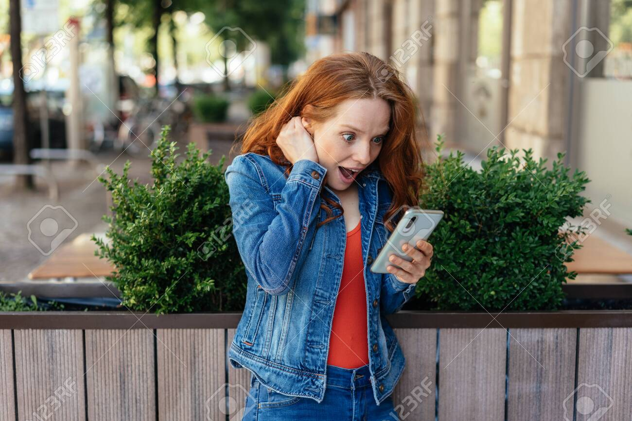 Young woman gawping at her mobile phone in astonishment as she reads a text message or streams media - 154410526