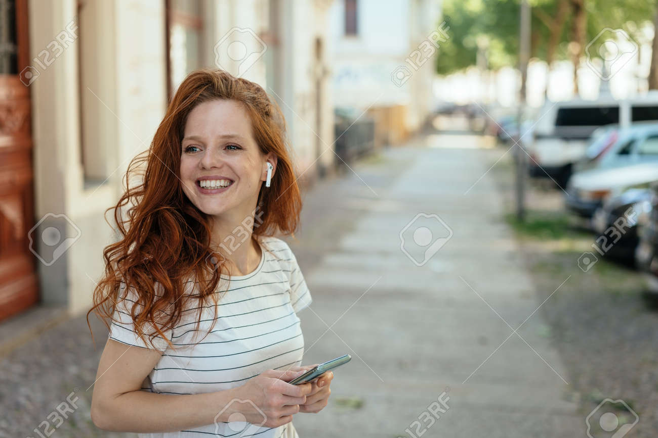 Happy young woman turning aside with a warm friendly smile as she stands waiting on a sidewalk in town - 154410537