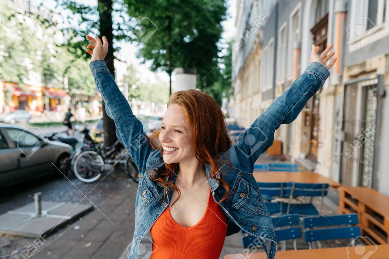 Happy casual young redhead woman rejoicing in town stretching up her arms and looking aside with a beaming smile of pleasure - 154410540