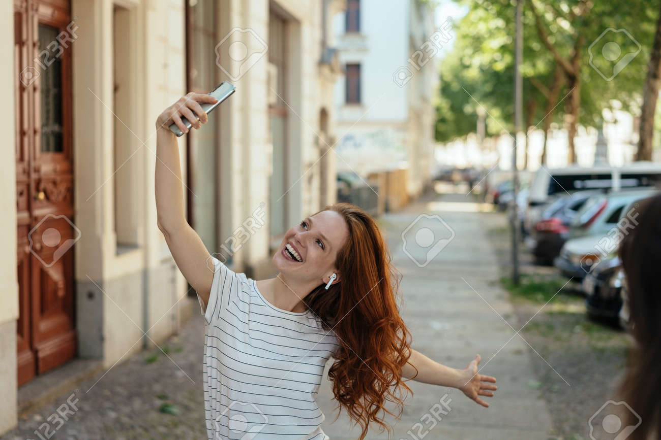 Vivacious young woman posing for a selfie on her smartphone on a quiet urban street grinning for the camera - 154410544