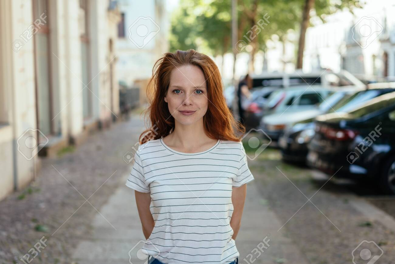 Young woman with a quiet attentive smile standing with hands behind her back on a quiet urban street in a frontal portrait - 154410575