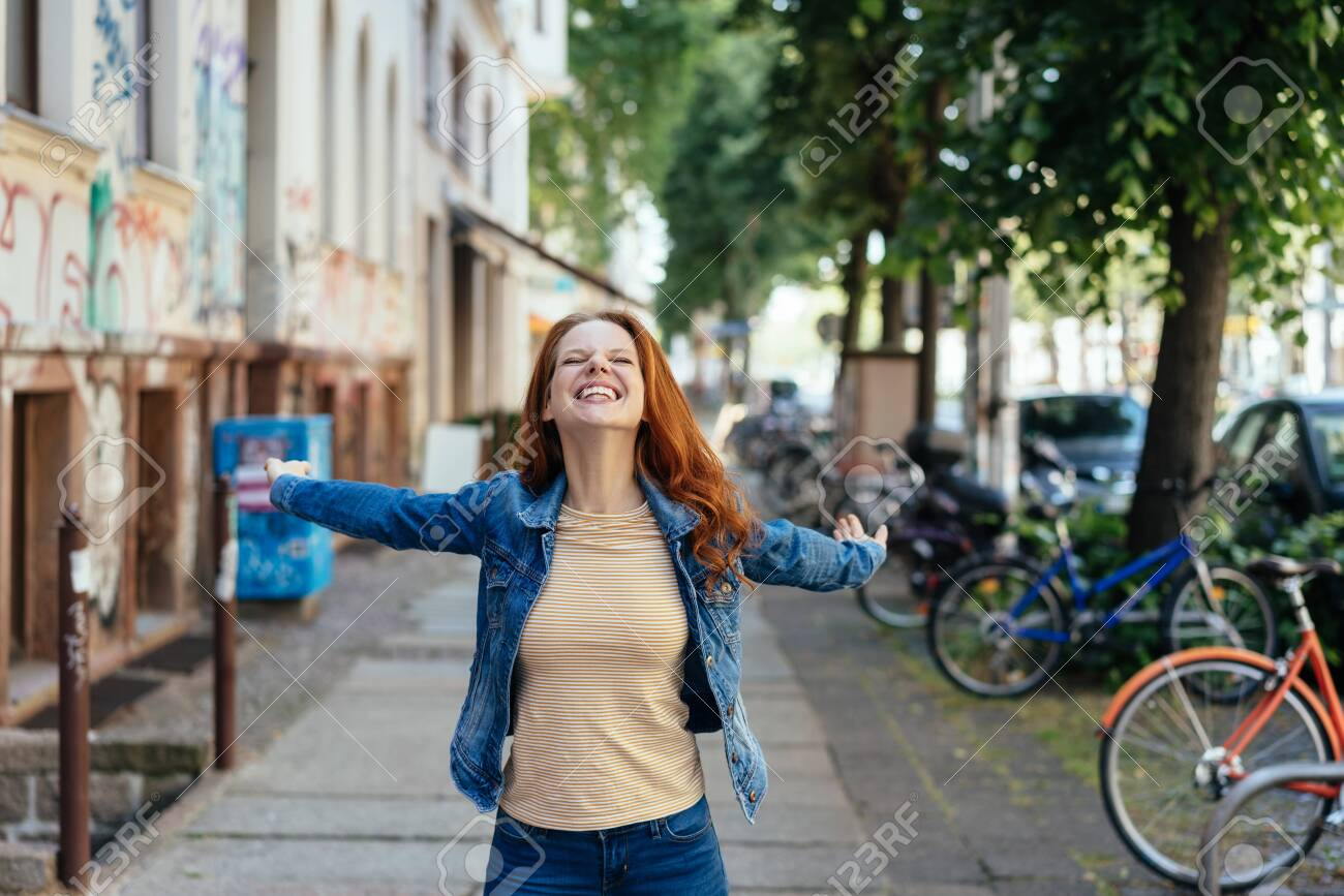 Happy young woman rejoicing with outstretched arms and a beaming smile on a sidewalk on a quiet urban street - 154410582