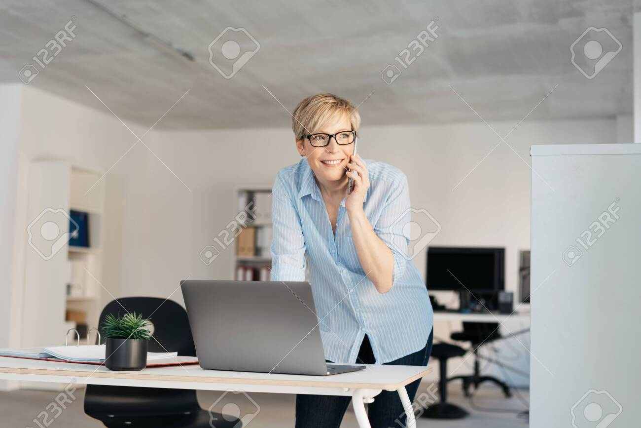 Smiling businesswoman with short haircut, in glasses and blue shirt, standing at the office desk in front of laptop, talking by mobile phone and looking aside. Low angle portrait with copy space - 153538866
