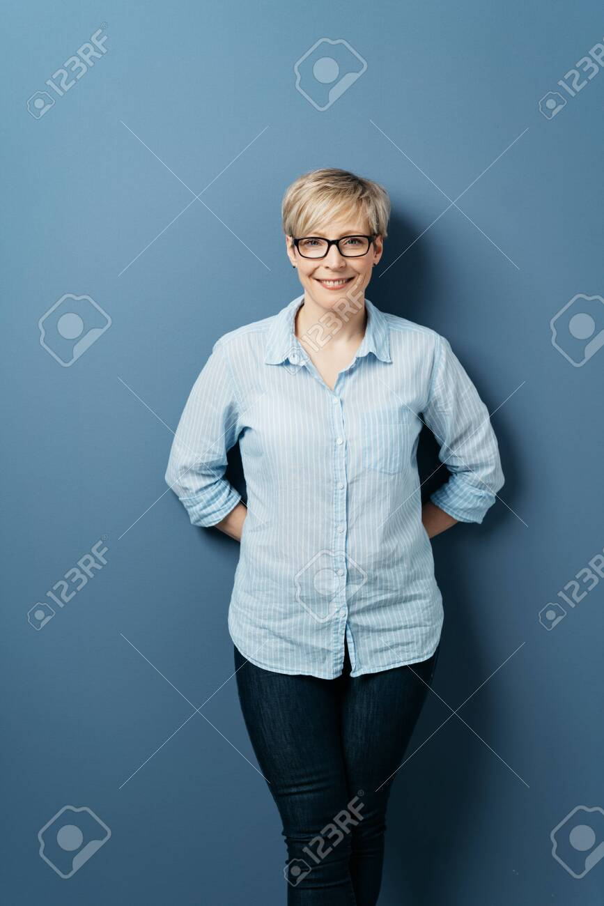 Front portrait of smiling middle-aged woman with short blond hair, wearing glasses, blue shirt and dark jeans, standing with her hands behind her back, against plain blue background in studio - 153539406