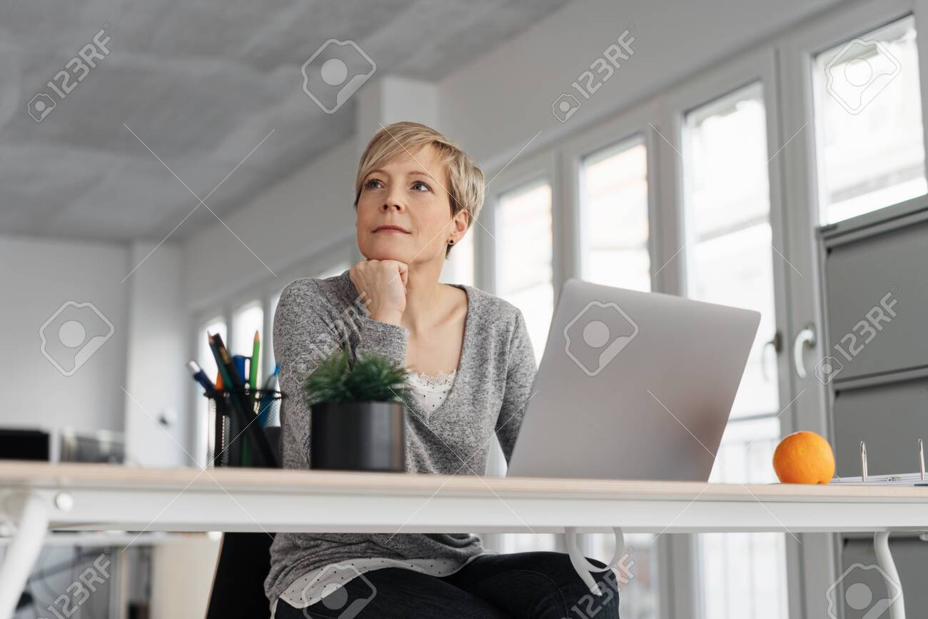 Thoughtful mature blonde woman sitting in front of computer at office - 153539274