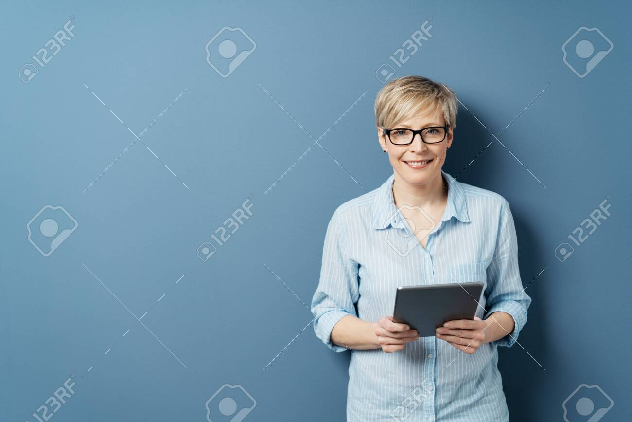 Smiling middle-aged woman with short blond hair, wearing glasses and blue shirt, standing with tablet computer in her hands and looking at camera. Front portrait on blue background with copy space - 153539368